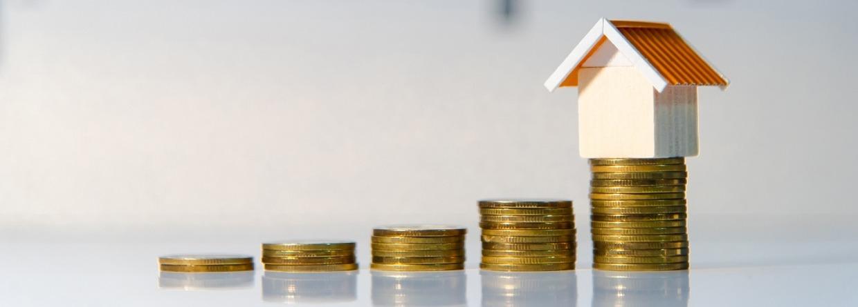 Oplopende stapel met munten geld en op de laatste stapel staat een huis